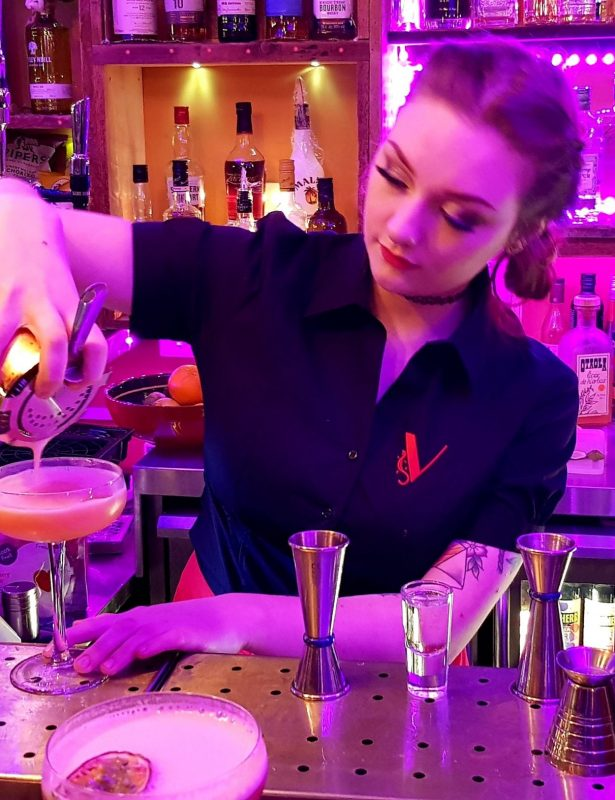 Young lady pouring cocktail embroidered blouse